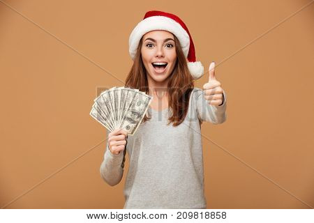 Image of excited caucasian lady with thumbs up wearing christmas hat standing isolated holding money. Looking camera.