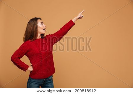 Photo of shocked caucasian woman dressed in sweater standing isolated. Looking aside and pointing.
