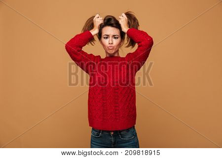Image of pretty caucasian woman dressed in sweater standing isolated showing funny emotions.