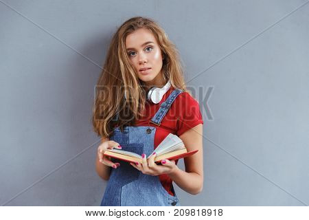 Young teenage girl holding book and looking at camera over gray wall background