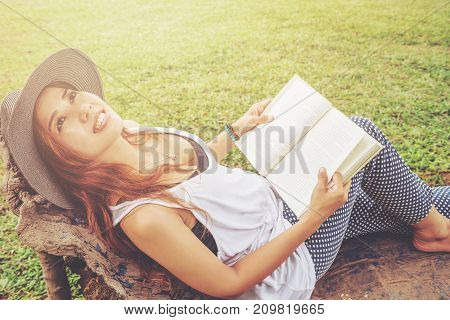 Asian women relax in the holiday. Read a book on the bench in the park.