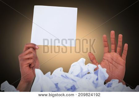 Heap of crumpled paper with hand holding blank page against orange background with vignette