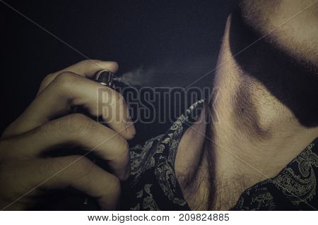 Unshaven guy in a shirt sprinkles on his neck perfume