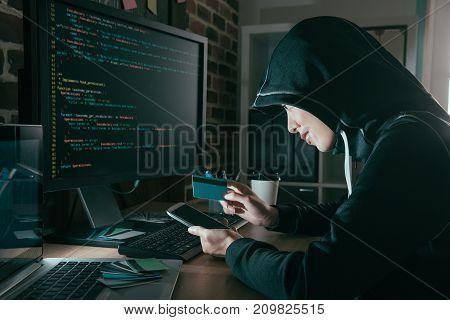 Hacker Holding Credit Card And Mobile Smartphone