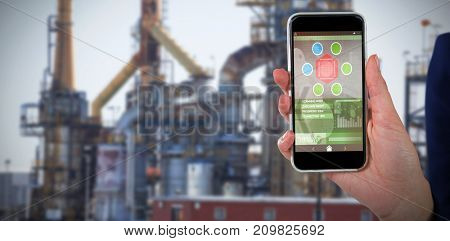 Mid section of businesswoman holding 3D mobile phone against image of factory