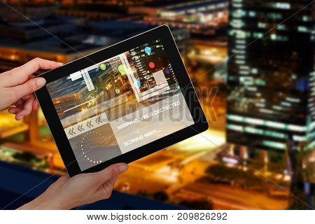 Hands holding digital 3D tablet against white background against illuminated road in city at night
