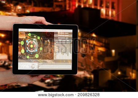 Close-up of hands holding digital 3D tablet against vehicles parked by building at night