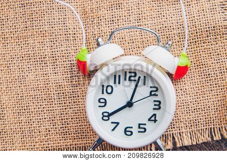 white alarm clock and red headphone in-ear on sack background