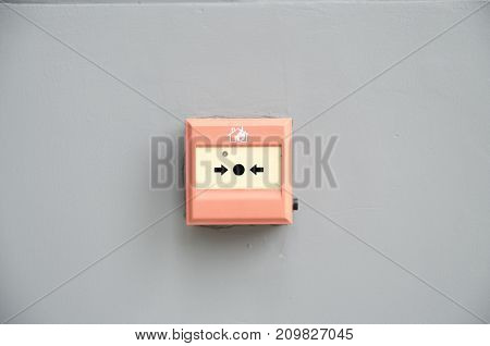 wall mounted Red fire alarm button used to activate warning systems in buildings