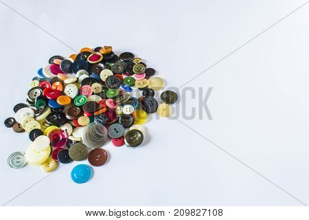 Many Different Buttons. Buttons For Clothes Made Of Plastic. Buttons Are Scattered On A Light Backgr