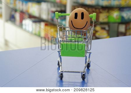 Egg happily smiling inside a mini trolley with blurred background of shop interior. Conceptual