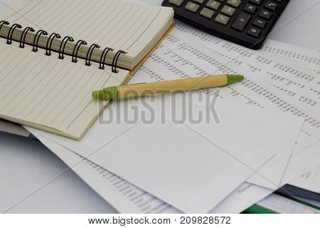Finance,auditing and accounting concept. Blank notebook, papers, pen, calculator and stack of accounting sheets on the table.