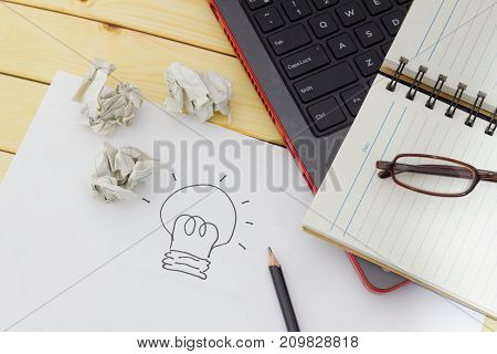 Ideacreativity and innovation concept. Spectacles blank notebook pencil laptop crumpled papers and a piece of white paper with a light bulb drawing on wooden table.