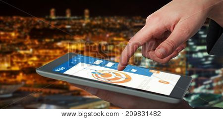 Businesswoman hand using digital 3D tablet against high angle view of illuminated crowded cityscape