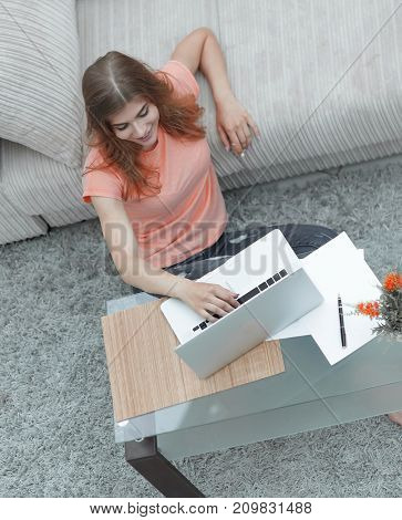 girl student working on laptop sitting on the carpet near the sofa.