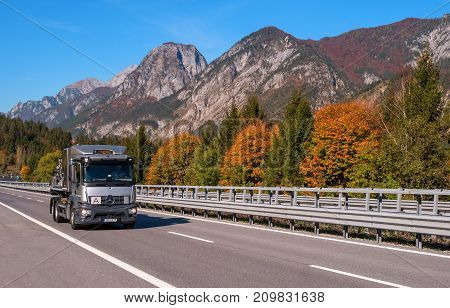 TYROL AUSTRIA - October 14 2017: A silver truck on a high-speed mountain road. In the background there are mountains and trees with red and yellow leaves.