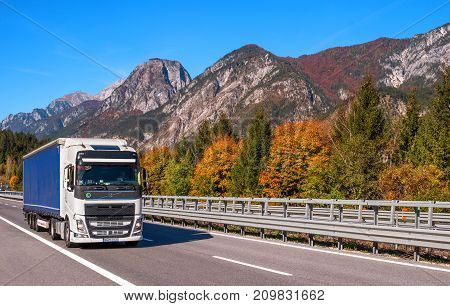 TYROL AUSTRIA - October 14 2017: A white blue truck on a high-speed mountain road. In the background there are mountains and trees with red and yellow leaves.