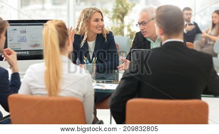 Group of confident business partners discussing paper at the meeting