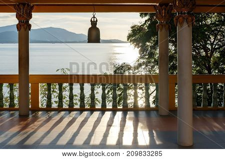 Terrace with columns, Buddhist bell, view of the sea and mountains in the distance. The rays of the pre-dawn sun are reflected in the water and create beautiful shadows. Thailand.
