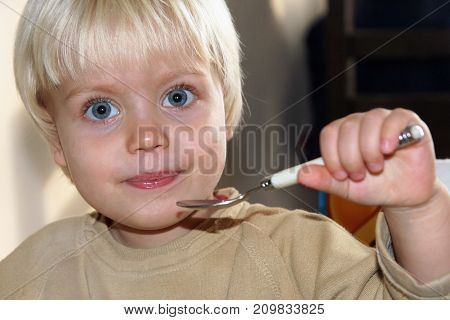 Cute little boy portrait, holds a spoon and looks straight into the camera with his big blue eyes