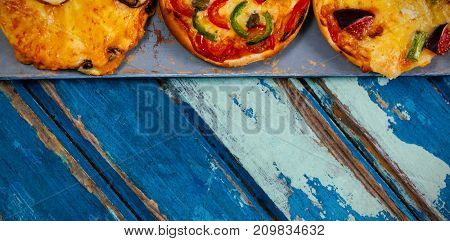 Overhead cropped image of pizzas on weathered wooden table