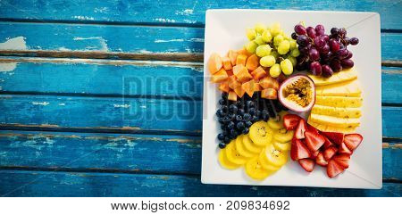 Overhead view of fresh fruits in white plate on blue wooden table