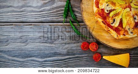 Overhead view of pizza by tomatoes and chili peppers on wooden table