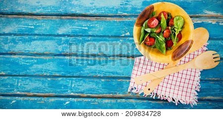 Overhead view of fresh salad in wooden bowl by spoon and fork with napkin on table