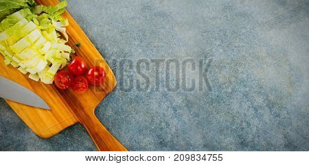 Overhead view of chopped lettuce with tomato on cutting board