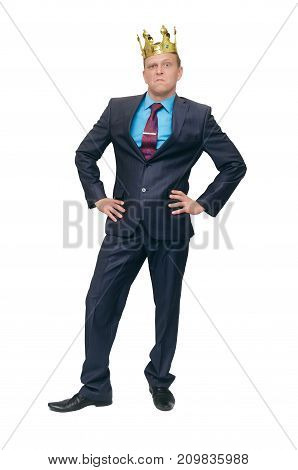 Dissatisfied conceited and arrogant man in a suit and crown on his head stands with his hands in his belt isolated on white background. Strict boss. Arrogant man.