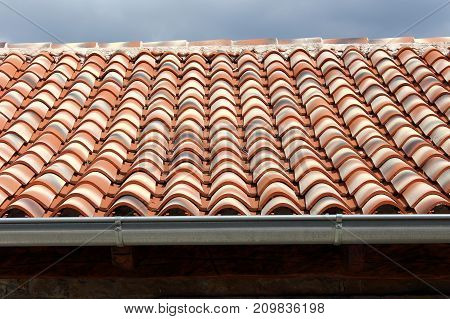 Newly put classical round roof tiles in various shades of colors, from red to grey and new rain drain on the edge