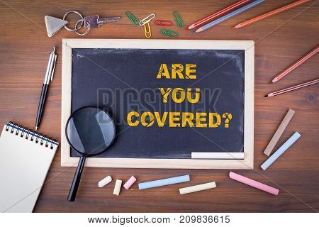 Are You Covered. On a wooden table chalk board.