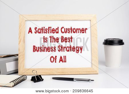 A Satisfied Customer Is The Best Business Strategy of All. Office table with wooden frame.