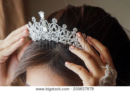 Luxury wedding crown diadem on bride's head hairstyle. morning wedding preparation bride with crown close up