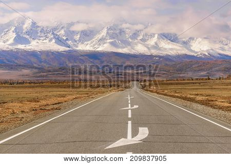 Beautiful autumn view with an asphalt road going through the steppe to the mountains covered with snow golden trees on the roadside and fluffy clouds