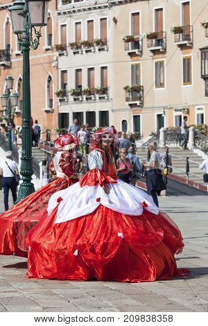 VENICE ITALY - SEPTEMBER 22 2017: Beautiful dressed women in traditional Venetian costume. The tradition of Venetian masks began in Venice in the 11th century