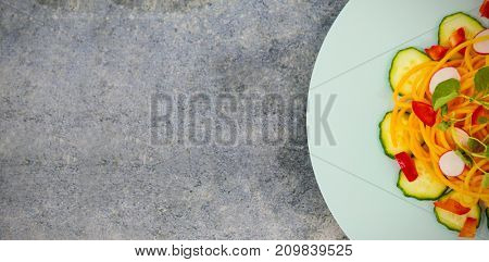 Overhead view of fresh salad in plate on gray table