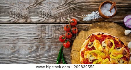 Overhead view of pizza by spices on wooden table