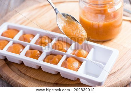 Ice tray with fresh fruit puree on wooden background