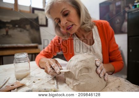 Attentive senior woman shaping a molded clay in drawing class