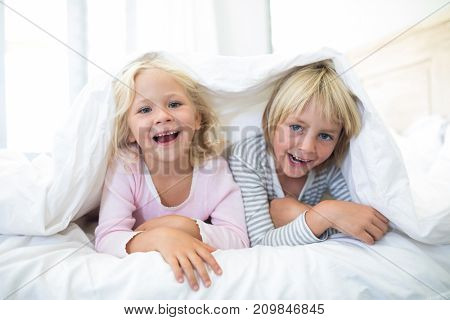 Portrait of happy siblings lying under blanket on bed in bedroom at home