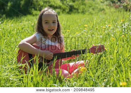 Portrait of cute girl playing guitar in field on a sunny day