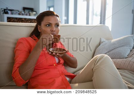 Thoughtful woman having coffee in the living room at home