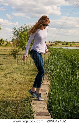 Beautiful young girl is teetering on a stone parapet near the river