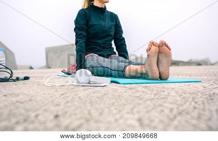 Unrecognizable woman exercising on mat by sea pier