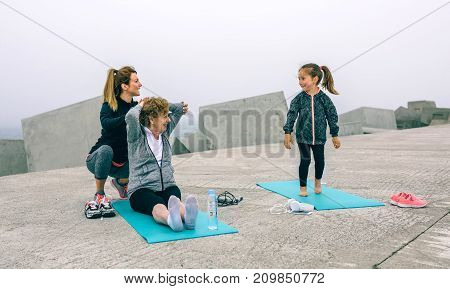 Young woman training girl and senior woman by sea pier