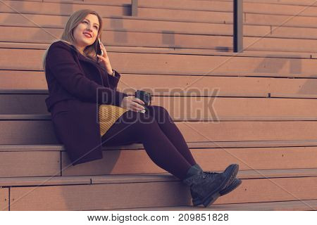 Cute atttactive woman drinking coffee while talking on her smart phone outdoors.