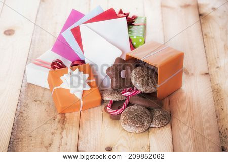 Gifts and envelopes on wooden table - Gingerbread in a gift box near a stack of gifts and multicolored envelopes