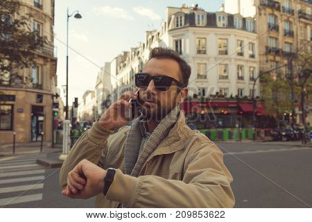Modern guy using cellphone and looking on his wrist watch in the European city.
