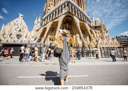 BARCELONA, SPAIN - August 16, 2017: Young woman tourist walking in front of the famous Sagrada Familia Roman Catholic church in Barcelona, designed by architect Antoni Gaudi